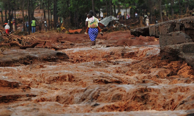 ایک خاتون اپنی پشت پر بچے کو باندھے محفوظ مقام کی جانب جارہی ہے، تصویر میں تباہی صاف دیکھی جاسکتی ہے—فوٹو: اے ایف پی