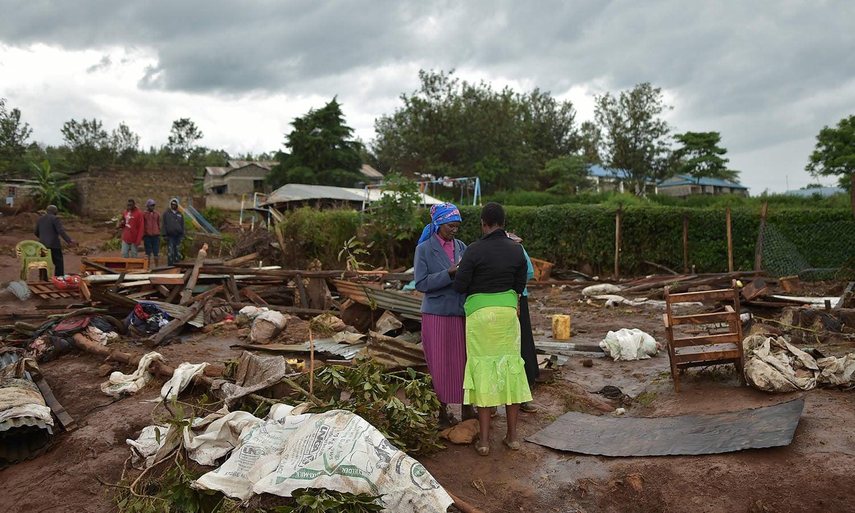 دو خواتین سیلاب کے باعث تباہ شدہ گھر کے ملبے سے ضروری اشیا اکھٹی کررہی ہیں—فوٹو: اے ایف پی