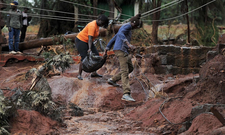 سیلاب سے تباہ حال راستوں اور کیچڑ  سے گزر تے ہوئے لوگ اپنا سامان منتقل کررہے ہیں—فوٹو: اے ایف پی