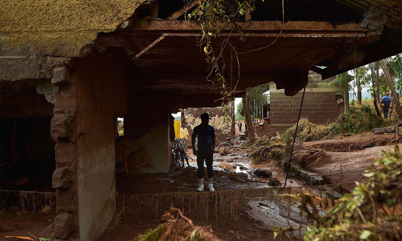 ایک شخص اپنے گھر کے تباہ شدہ حصے میں حسرت و یاس کی تصویر بنے کھڑا ہے—فوٹو: اے ایف پی