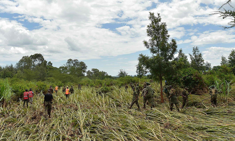 رضاکار اور کینیاکے فوجی تباہ شدہ فصلوں میں لاشیں تلاش کررہے ہیں —فوٹو: اے ایف پی