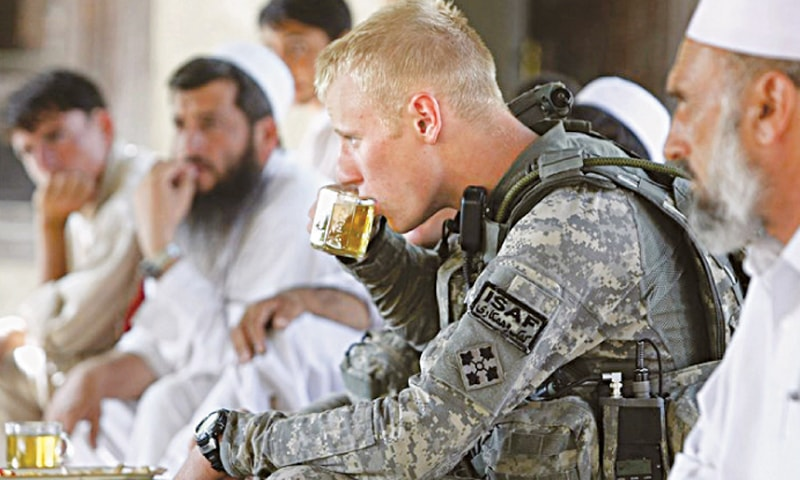 A US soldier drinks tea with Afghan villagers. Washington's mistakes have resulted in the deaths of hundreds of thousands of Afghans and Americans over the past 16 years |  Reuters