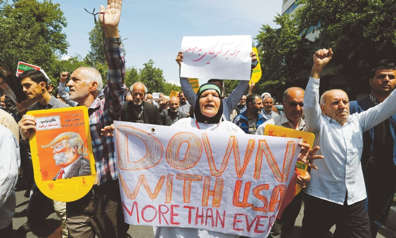 IRANIANS hold placards with anti-US slogans during a demonstration after Friday prayer in Tehran.—AFP