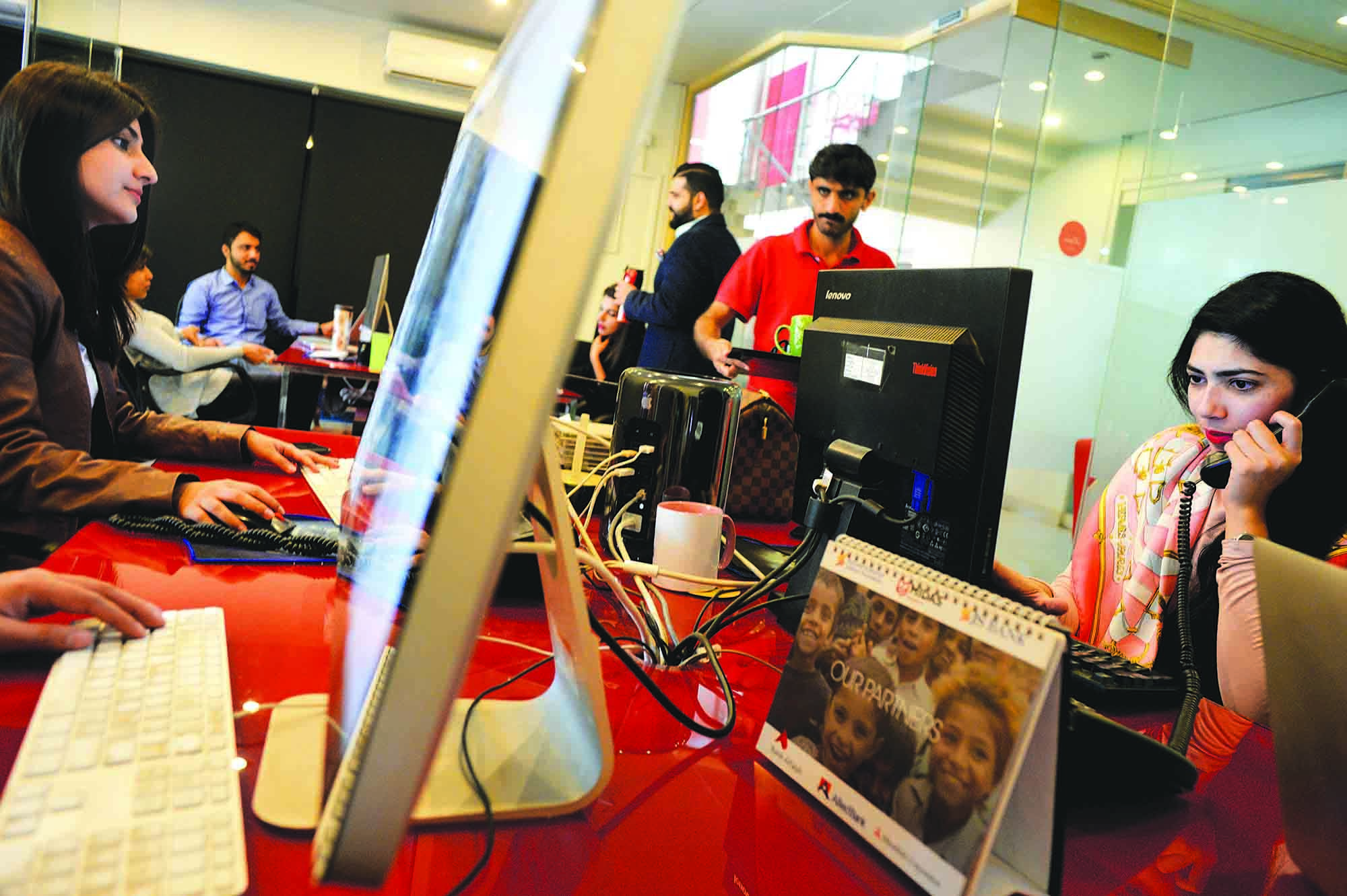 Millennials are busy on their devices during a working day at Ogilvy Pakistan, where the average age of all new recruits is approximately 25. For the agency, the secret to attracting Millennials is to offer them flexibility in their working hours and an informal environment. They are pluralists and not inclined to settle on only one thing; they want to do something in the day and something else completely different in the evening. To retain them, employers must always encourage and mentor them in any activity they choose to engage in after working hours. They have great expectations of life. (photo: Arif Mahmood/ Dawn White Star)