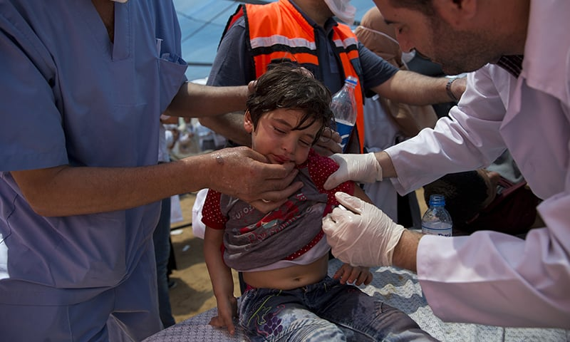 Medics treat a Palestinian child suffering from teargas inhalation during a protest near Beit Lahiya, Gaza Strip. — AP