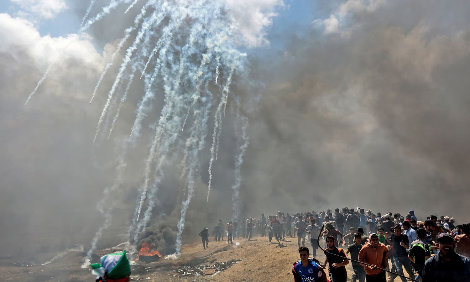 Palestinians run for cover from teargas fired by Israeli forces near the border between the Gaza strip and Israel. — AFP