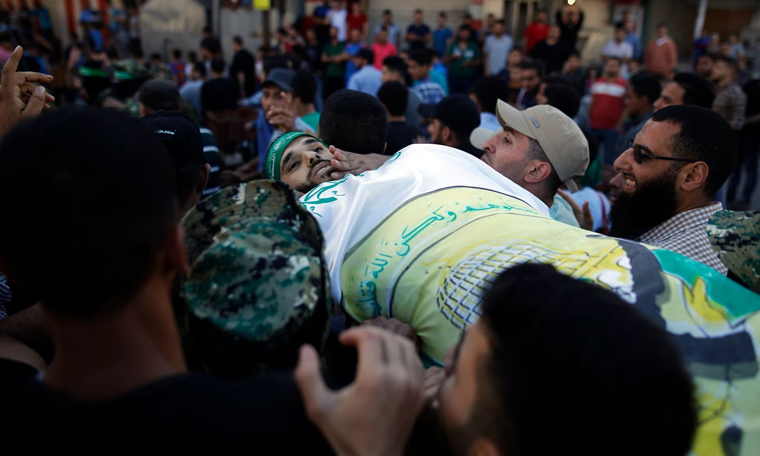 Palestinian mourners carry the body of man who was killed during clashes with Israeli forces. — AFP