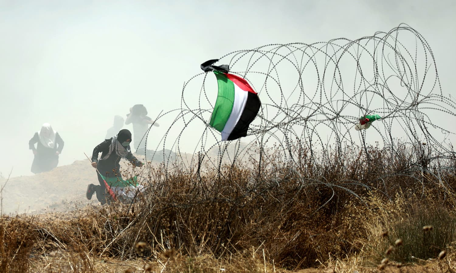 A Palestinian protester holding his national flag runs past barbed wires during clashes with Israeli forces near the border between the Gaza strip and Israel east of Gaza City. — AFP