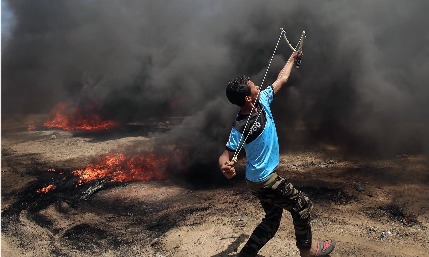 A Palestinian man uses a slingshot during clashes with Israeli forces along the border with the Gaza strip east of Khan Yunis. — AFP