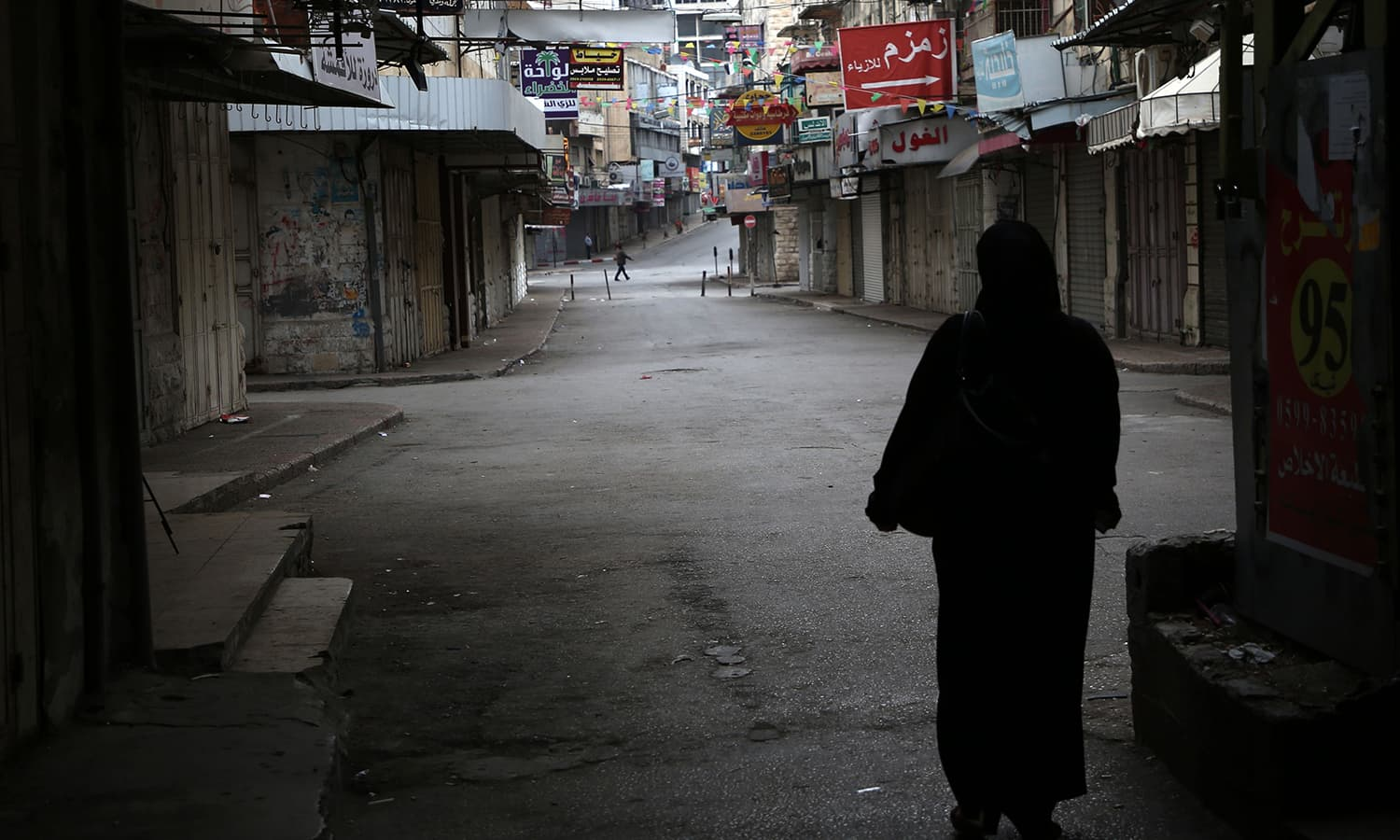 A Palestinian woman walks along an empty street in the Israeli occupied West Bank city of Nablus. — AFP