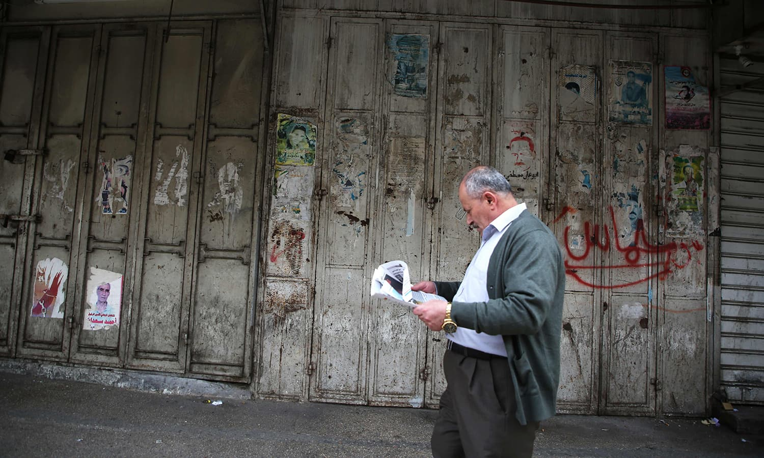 A Palestinian man walks past closed shops on an empty street in the Israeli occupied West Bank city of Nablus. — AFP