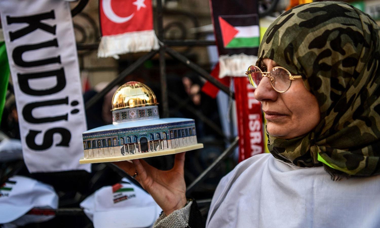 انقرہ میں اسرائیلی سفارتخانے کے باہر  ایک خاتون مسجد اقصیٰ کا ماڈل اٹھائے احتجاج میں شریک ہیں — فوٹو: اے ایف پی