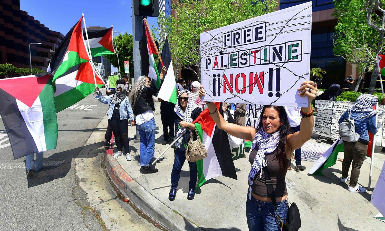 امریکا میں اسرائیلی سفارتخانے کے باہر خواتین فلسطینی پرچم کے ساتھ احتجاج کرتے ہوئے — فوٹو: اے ایف پی