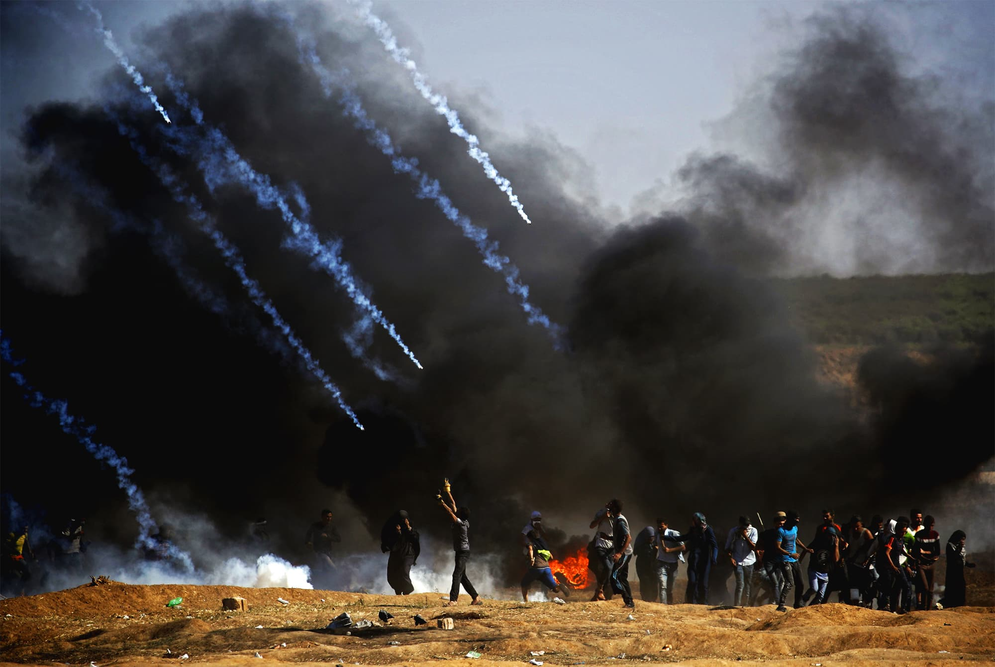 Tear gas is fired at protestors during clashes with Israeli forces near the border between the Gaza strip and Israel, east of Gaza City on May 14, 2018, following the the controversial move to Jerusalem of the United States embassy.  Fifty-two Palestinians were killed by Israeli fire during violent clashes on the Gaza-Israel border coinciding with the opening of the US embassy in Jerusalem, the health ministry in the strip announced. ─ AFP