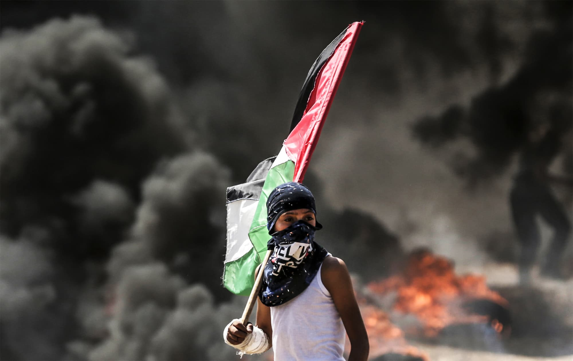 A Palestinian boy holding his national flag looks at clashes with Israeli security forces near the border between the Gaza Strip and Israel east of Gaza City on May 14, 2018. — AFP