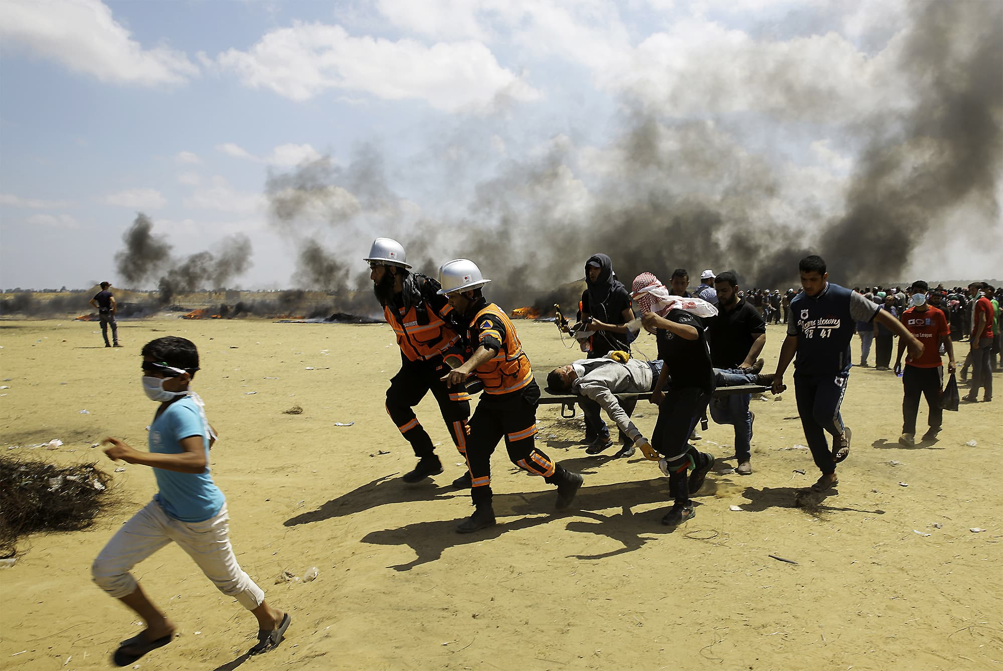 Palestinian medics and protesters evacuate a wounded youth during a protest at the Gaza Strip's border with Israel. ─ AP