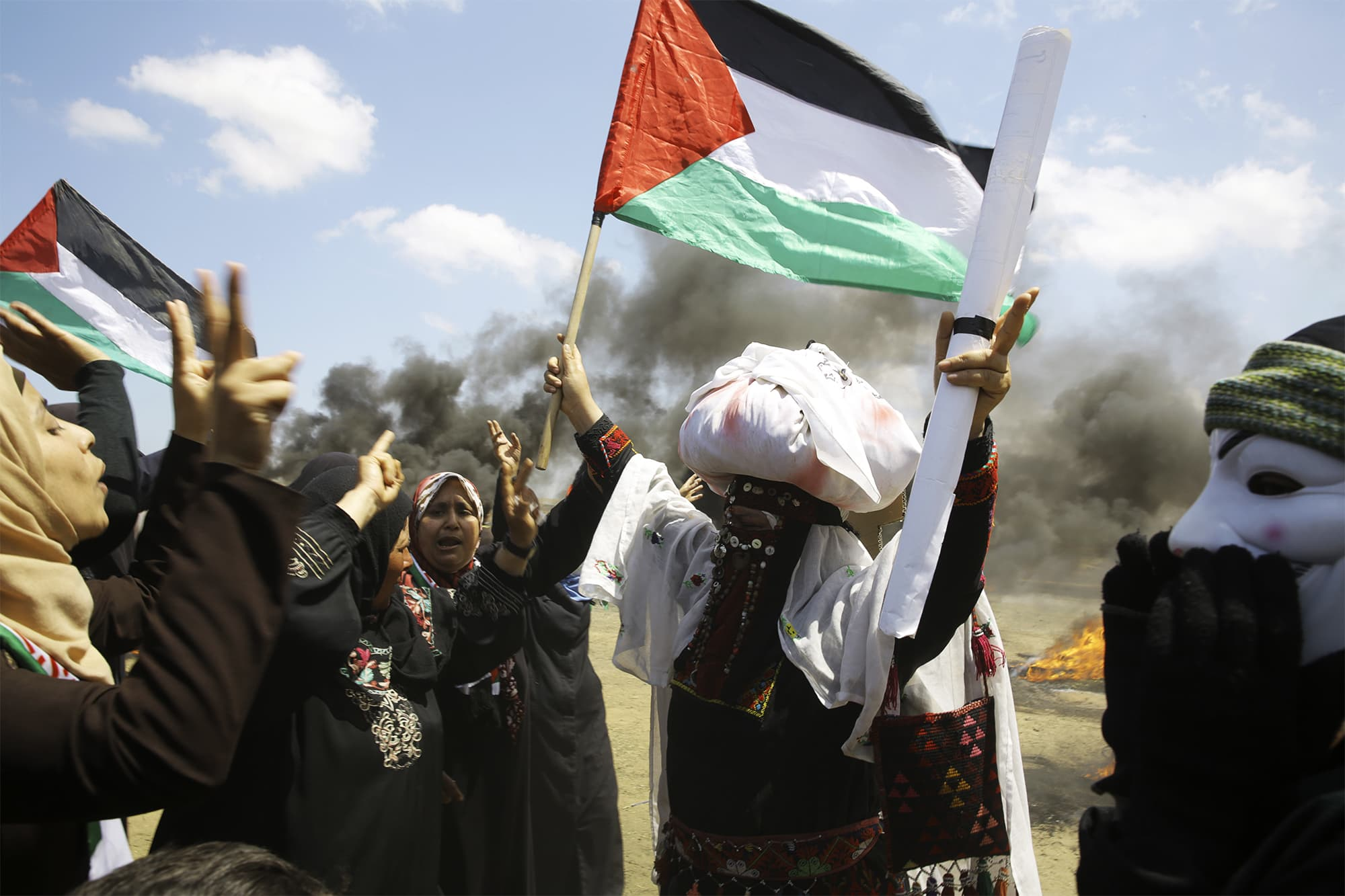 Palestinian women wave national flags and chant slogans near the Israeli border fence, east of Khan Younis, in the Gaza Strip, Monday, May 14, 2018. ─ AP