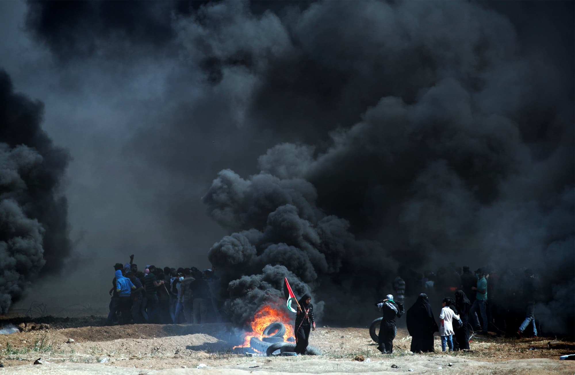 Palestinians burn tyres as they clash with Israeli forces near the border between the Gaza strip and Israel. — AFP