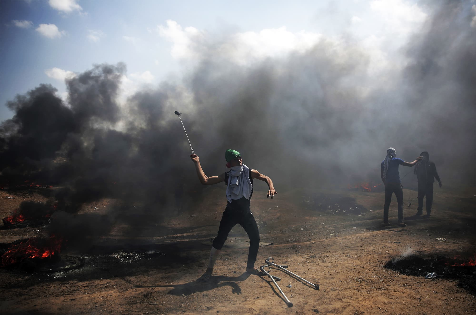Palestinian protesters hurl stones at Israeli troops during a protest on the Gaza Strip's border with Israel. ─ AP