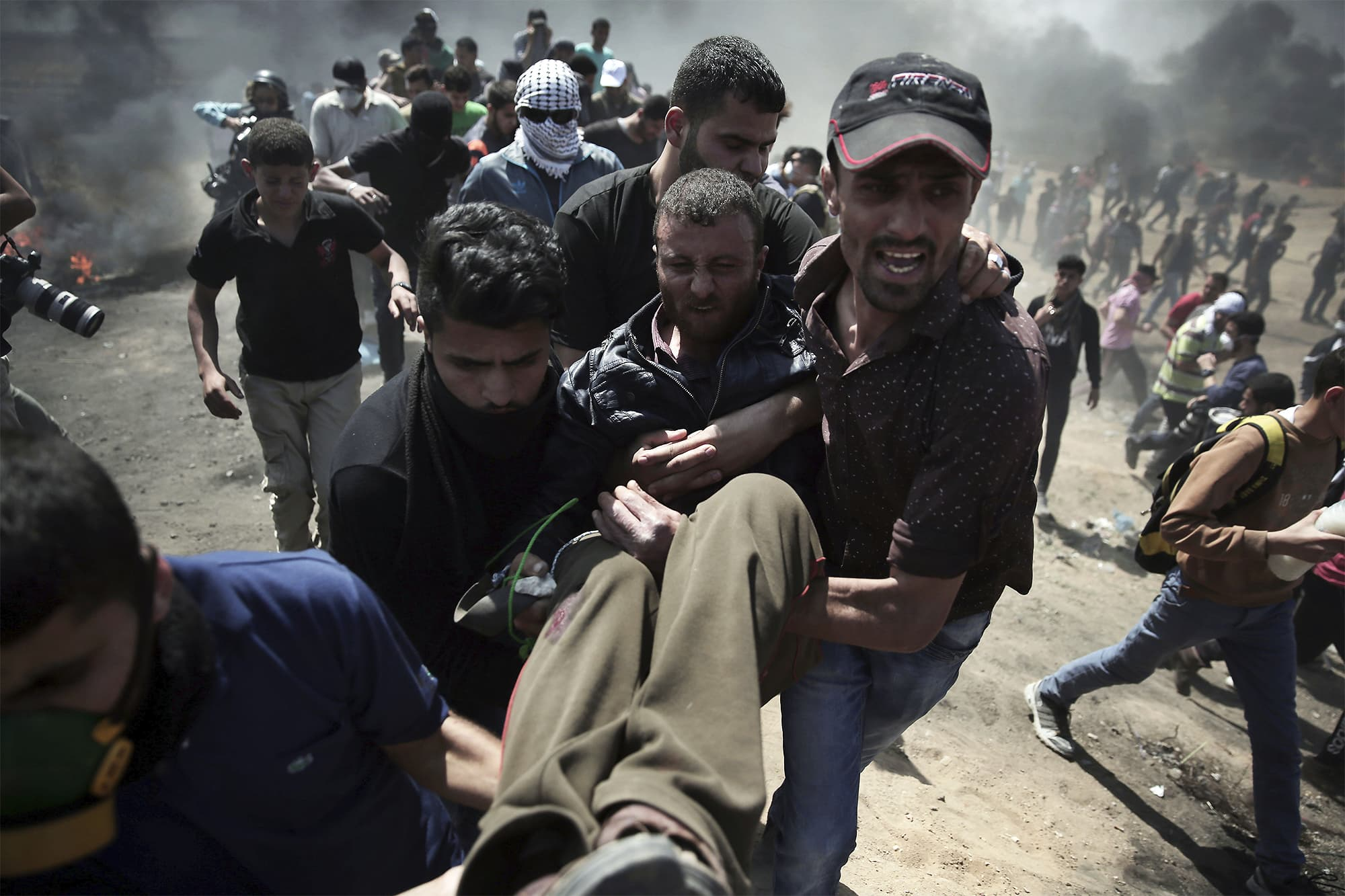 Palestinian protesters carry an injured man who was shot by Israeli troops during a protest at the Gaza Strip's border with Israel. ─ AP