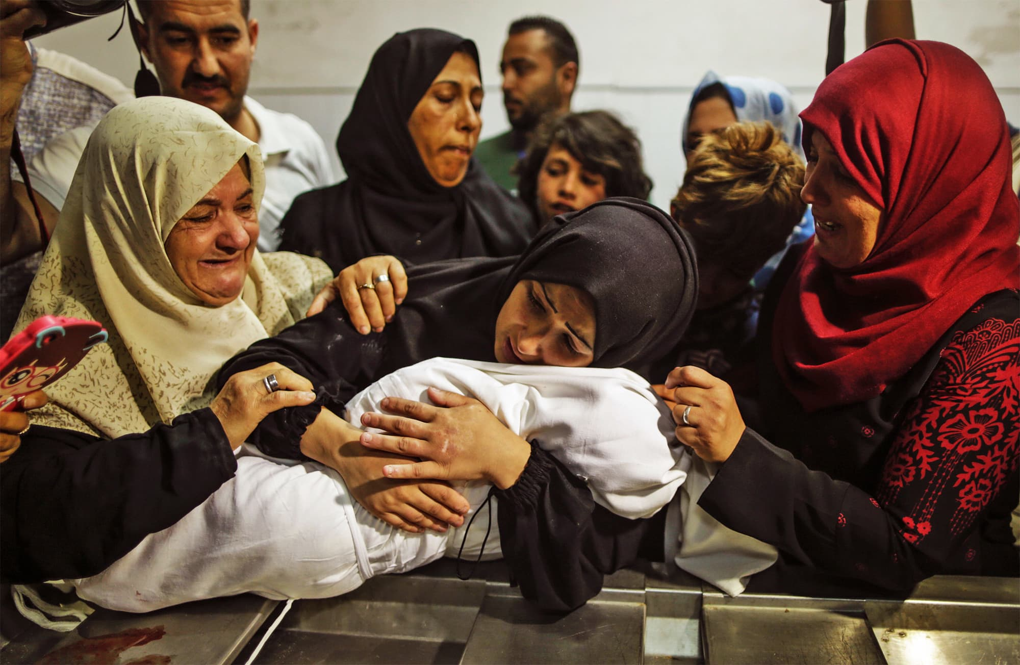 The mother (C) of Leila Al Ghandour, a Palestinian baby of 8 months who, according to the Palestinian Health Ministry died of tear gas inhalation during clashes in East Gaza the previous day, holds her at the morgue of Al Shifa hospital in Gaza City on May 15, 2018. — AFP