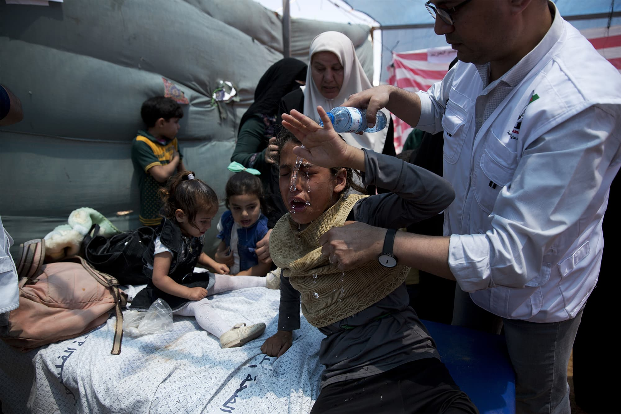 Medics treat Palestinian children suffering from teargas inhalation during a protest near Beit Lahiya, Gaza Strip on Monday, May 14, 2018. ─ AP