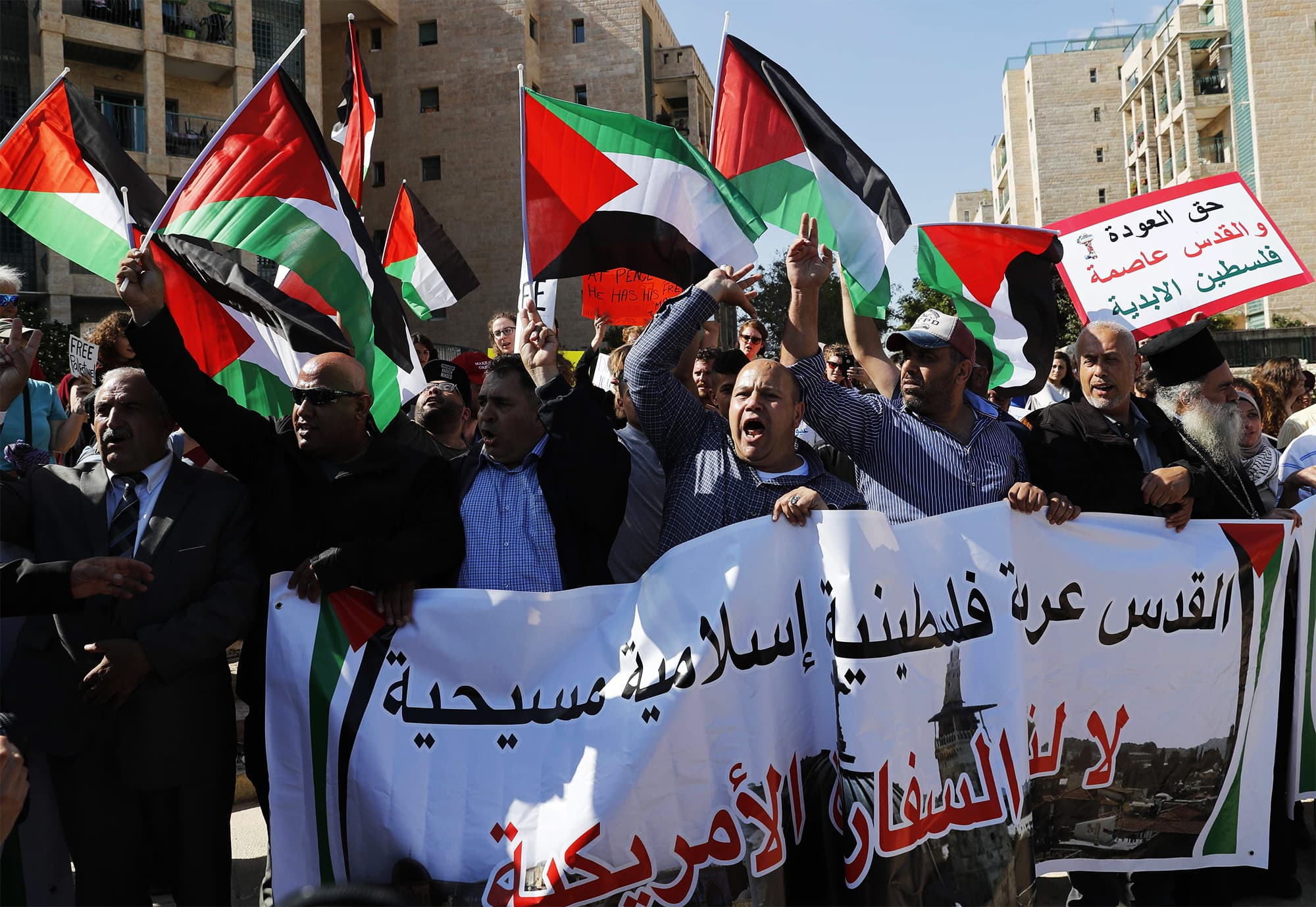 "Arab demonstrators protest in front of the new US embassy in Jerusalem on May 14, 2018. The banner reads in Arabic: ""Jerusalem is Arab, Palestinian, Muslim, Christian."" — AFP"