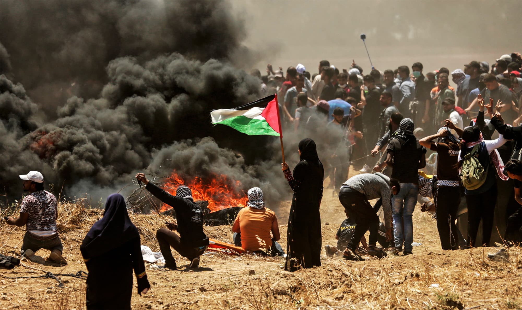 A Palestinian woman holding her national flag looks at clashes with Israeli forces near the border between the Gaza strip and Israel on May 14, 2018. — AFP