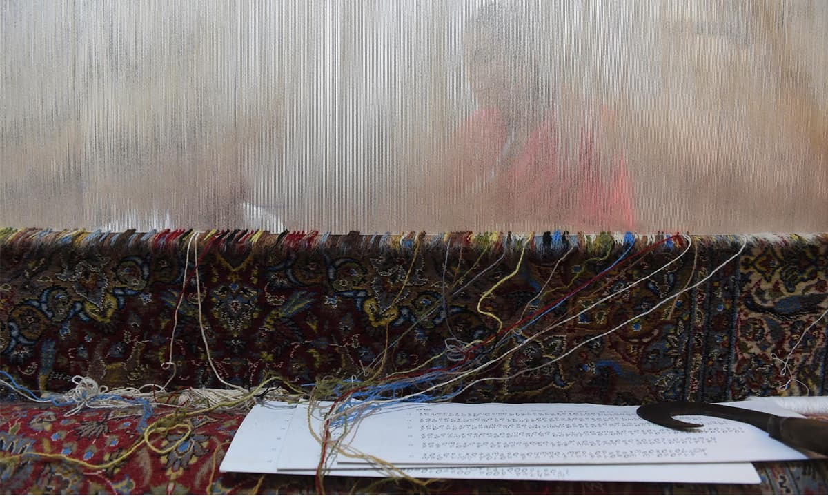 An unfinished carpet on the loom
