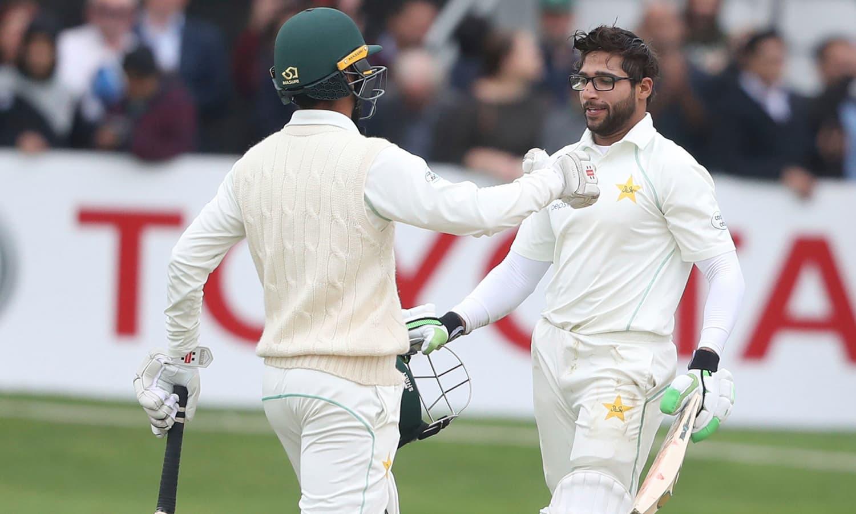 امام الحق کو عمدہ اننگز کھیلنے پر ساتھی کھلاڑی شاداب خان مبارکباد دے رہے ہیں— فوٹو: اے پی