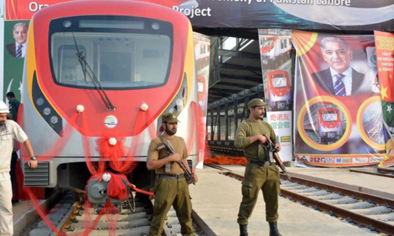 دو پولیس اہلکار ٹرین کی حفاظت کے لیے چاک و چوبند کھڑے ہیں —فوٹو: عدنان شیخ