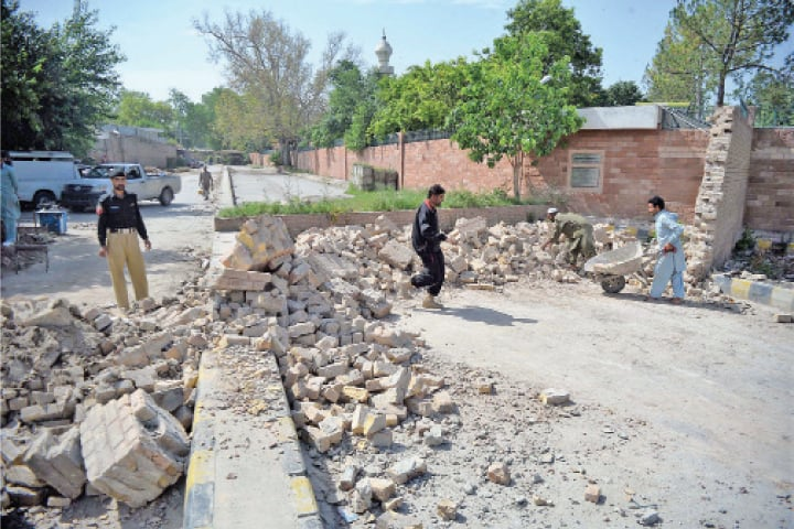 Workers demolish a security wall on Fort Road, Peshawar, on Wednesday. — Photo by Shahbaz Butt
