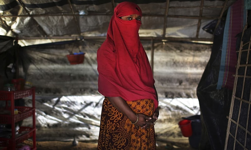 F, 22, who says she was raped by members of Myanmar's armed forces in June and again in September, clutches her hands around her pregnant belly as she is photographed in her tent in Kutupalong refugee camp. — AP