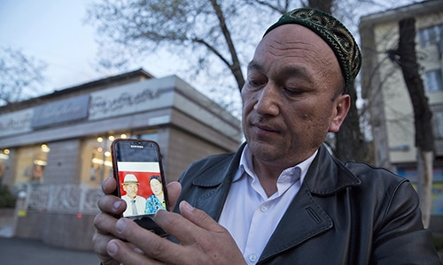 Omir Bekali holds up a mobile phone showing a photo of his parents whom he believes have been detained in China. — AP