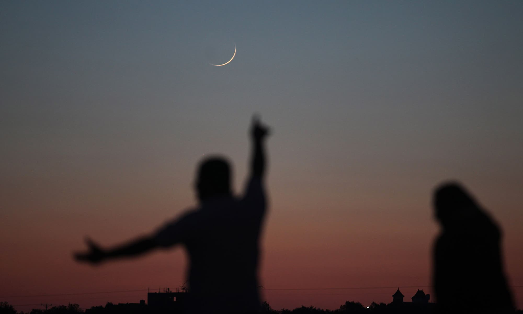 A Palestinian man points towards the moon in its Crescent form in Khan Yunis in the southern Gaza Strip. — AFP