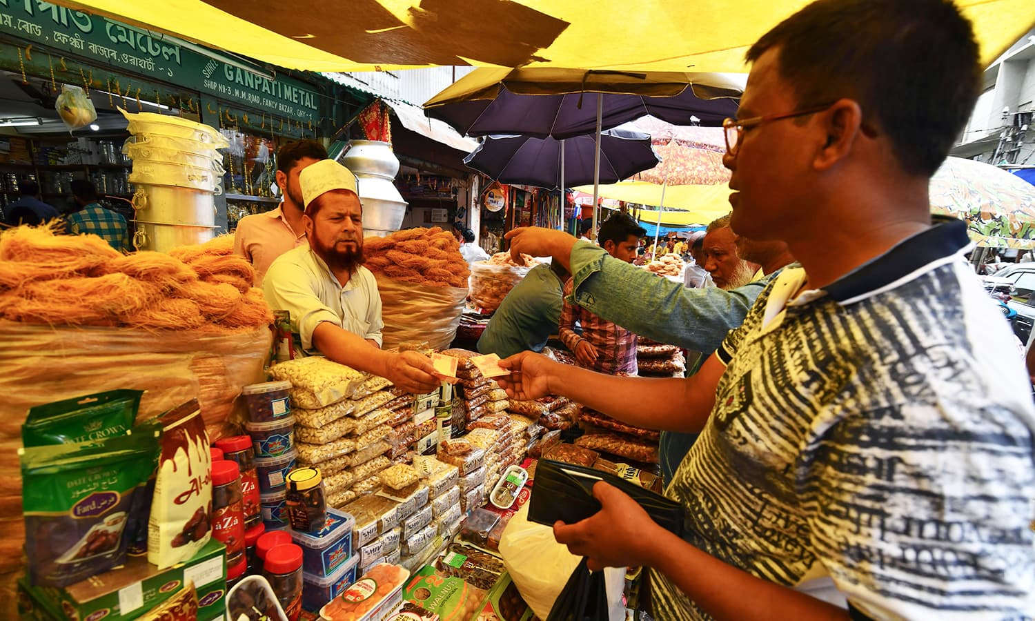 An Indian Muslim vendor sells dry food on the eve of the month of Ramazan at a market in Guwahati. — AFP