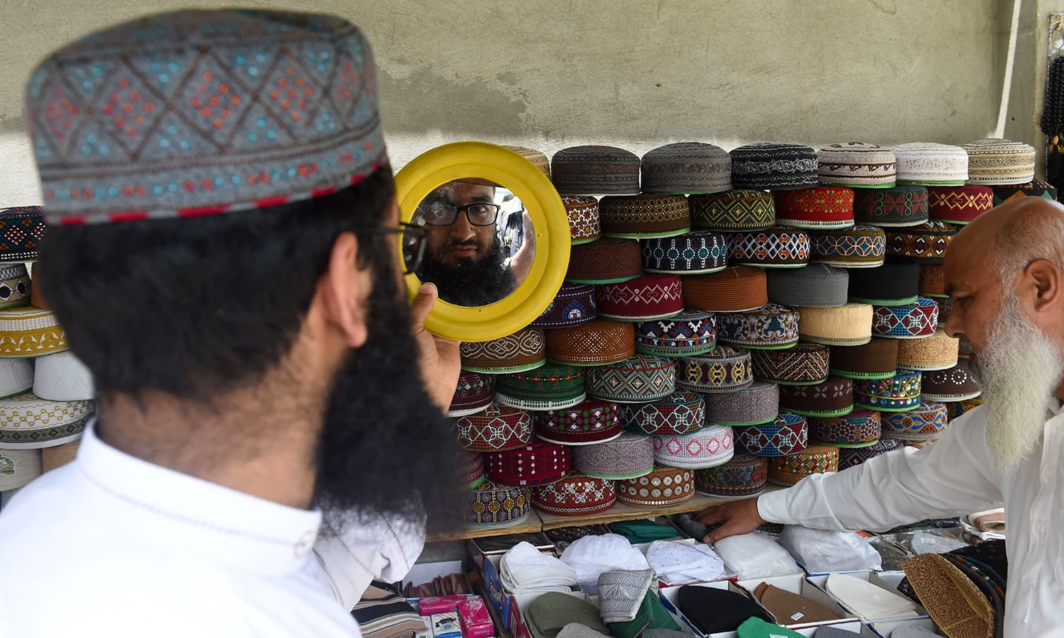 A Pakistani man looks at prayer caps at a roadside stall ahead of the Muslim fasting month of Ramazan in Lahore. — AFP