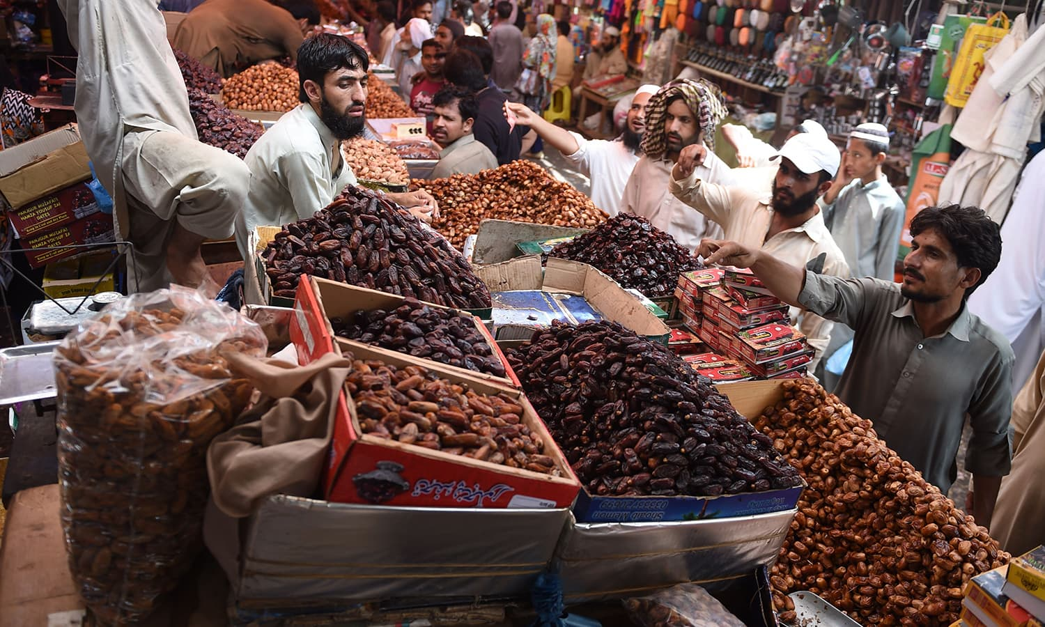 Pakistani Muslims buy dates at a market ahead of Ramazan. — AFP
