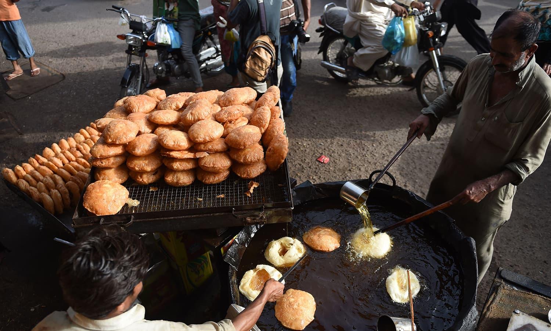 Pakistani vendors prepare vermicelli for customers ahead of the Muslim fasting month of Ramazan in Karachi. — AFP