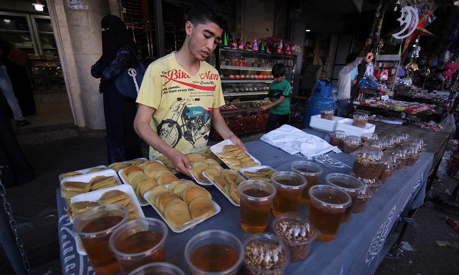 "A Palestinian boy sells ""Qatayef"", traditional pancakes that are popular during the Muslim fasting month of Ramazan, at a market in Khan Yunis in the southern Gaza Strip. — AFP"