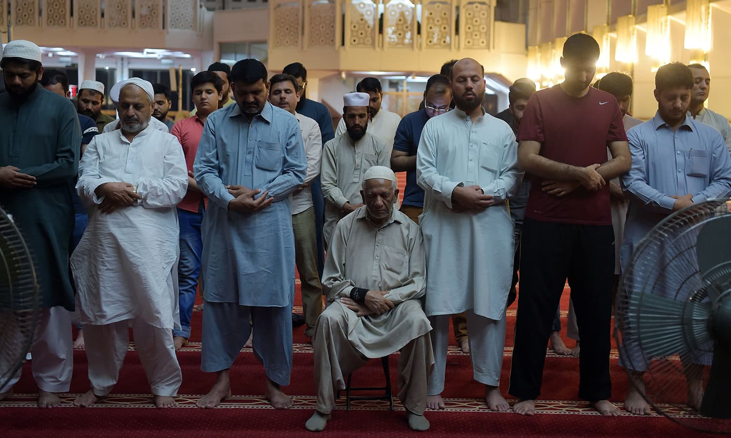 "Pakistani Muslims attend a special ""Taraweeh"" evening prayer on the first day of Ramazan at the Grand Faisal Mosque in Islamabad. — AFP"