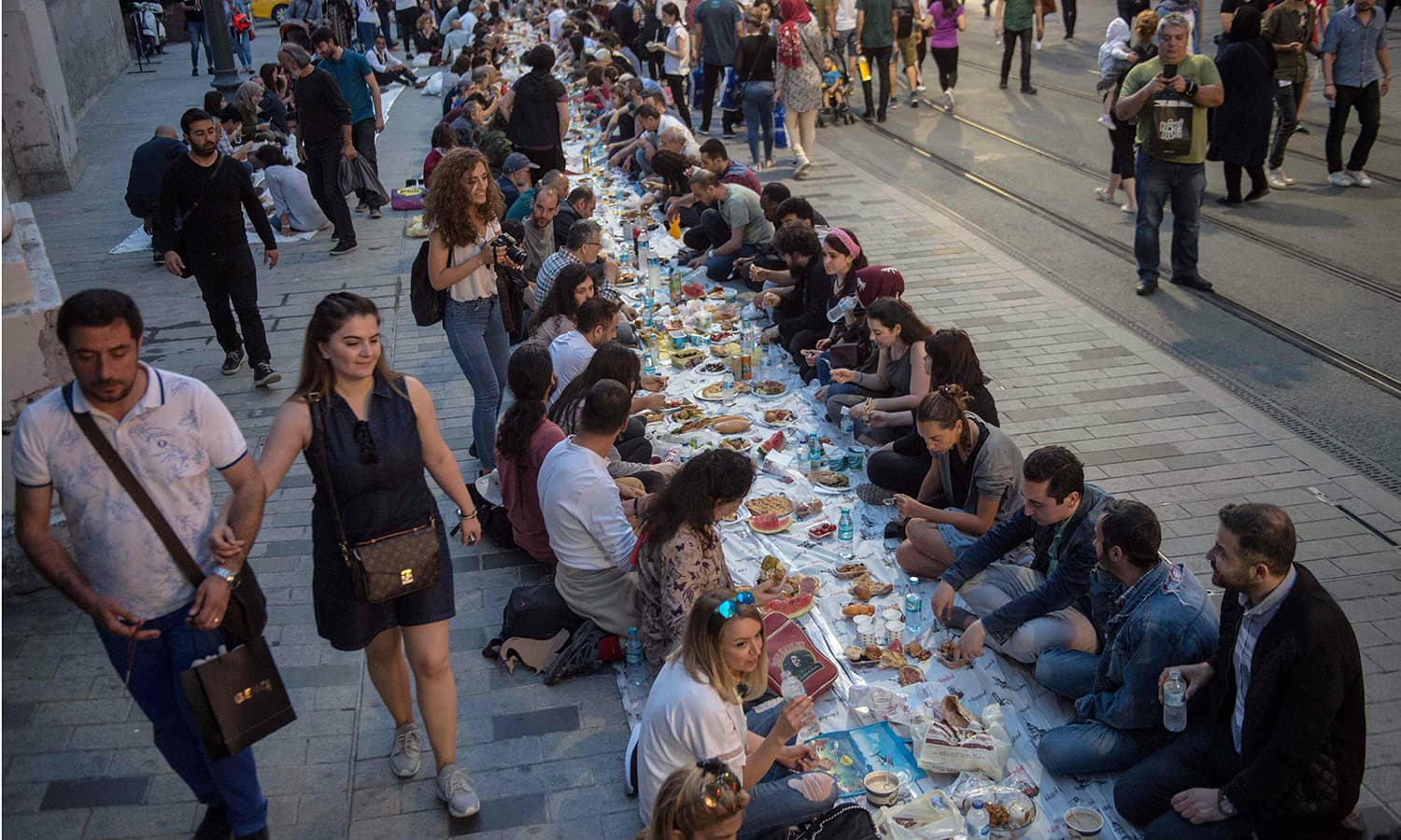 People break their fast on May 16 near Taksim Square in Istanbul, Turkey during the first day of the holy month of Ramazan. — AFP