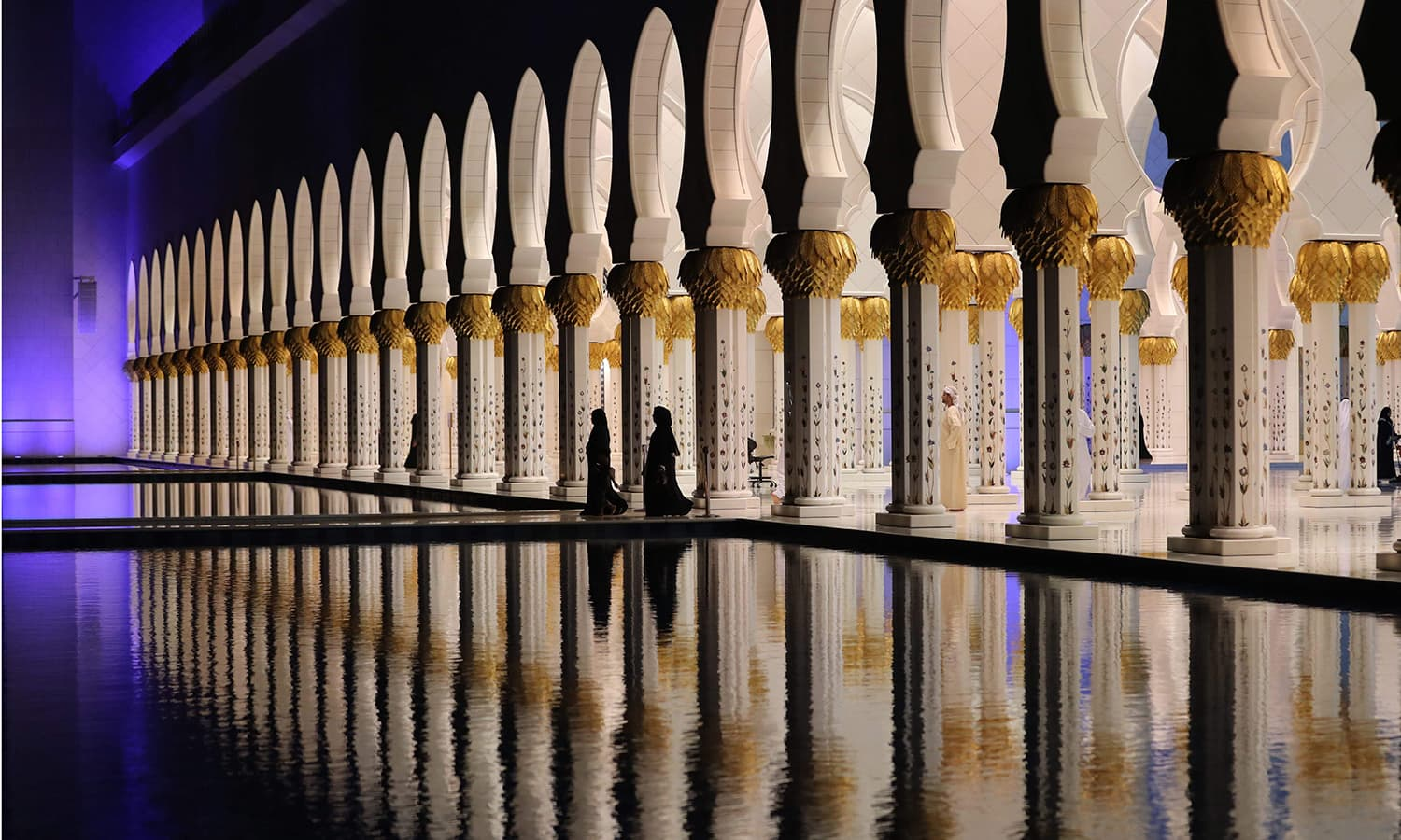 A picture taken on May 16, 2018 shows people walking at the Sheikh Zayed Grand Mosque in Abu Dhabi as Muslims start the holy fasting month of Ramazan. — AFP