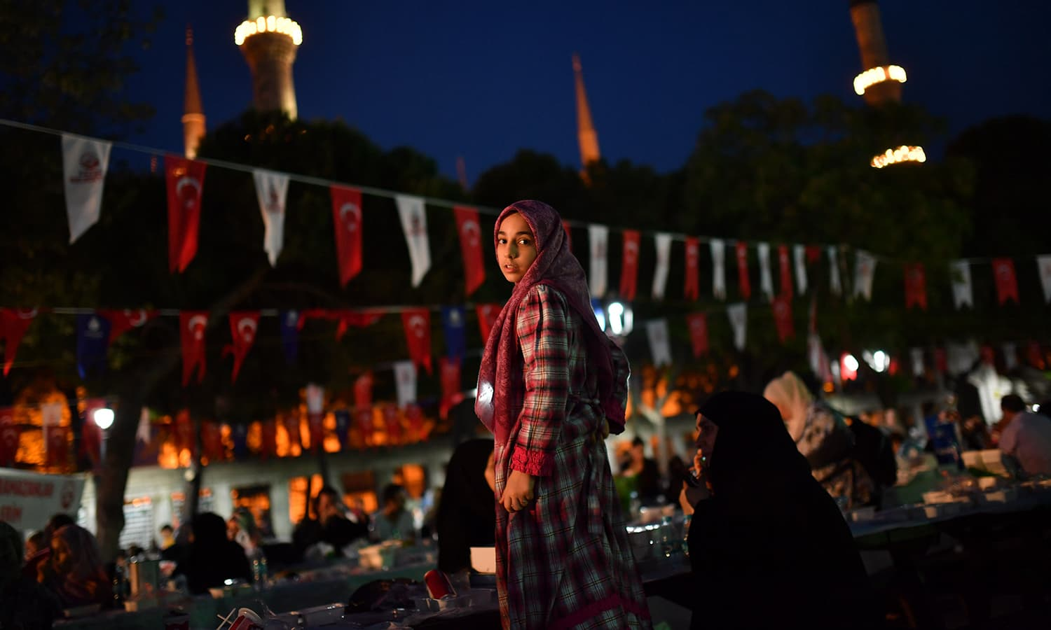 A Turkish girl stands as people begin to break the fast on the first day of Ramazan in front of Blue Mosque at Sultanahmet in Istanbul on May 16. — AFP