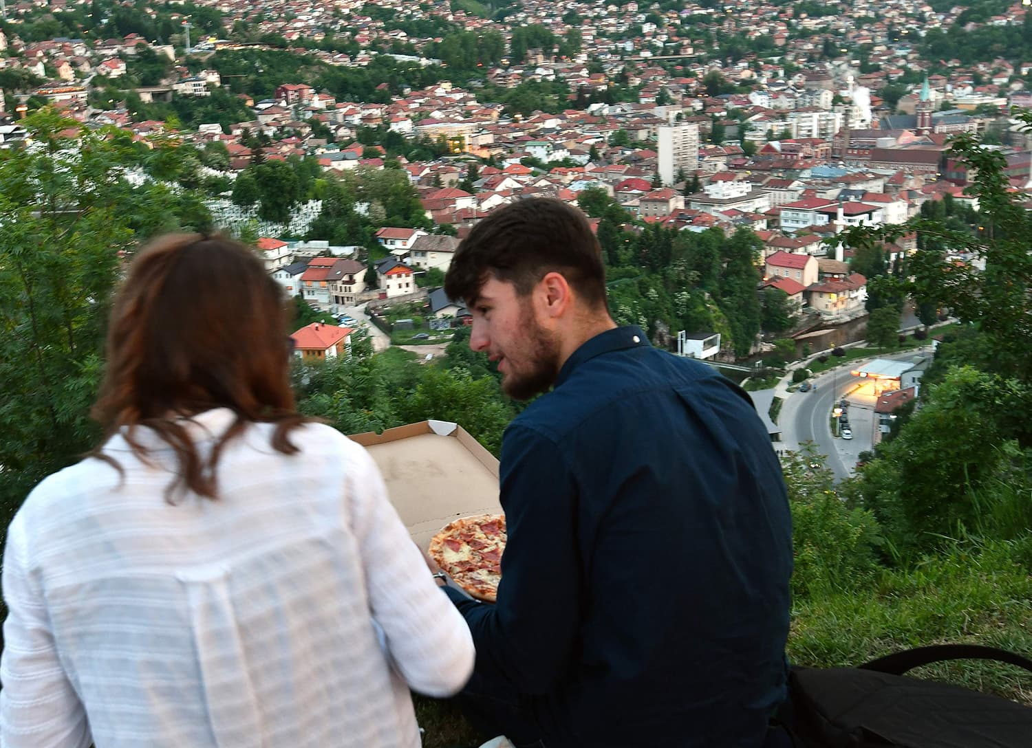 A Bosnian Muslim couple sits on the ground overlooking the city and share a pizza, at the end of daily fasting on the first day of the holly month of Ramazan, in Sarajevo on May 16. — AFP