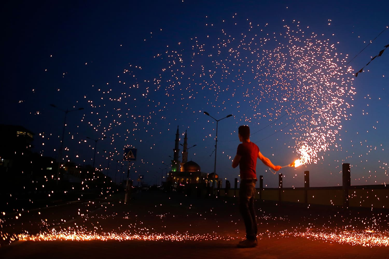 A Palestinian youth waves a sparkler next a mosque in Gaza City on May 16. — AFP