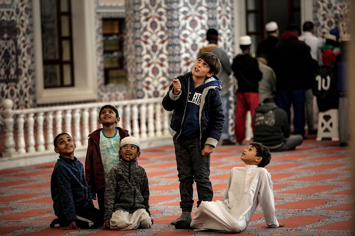 Boys look up as Muslim worshippers pray the first Taraweeh evening prayer on the first day of the Muslim fasting month of Ramazan at the Nizamiye Mosque in Midrand, Johannesburg. — AFP