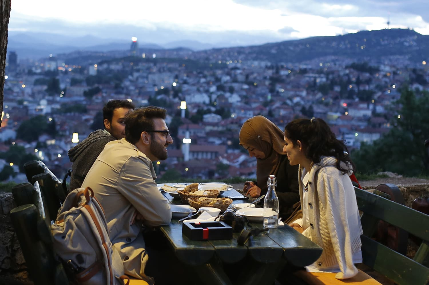 A group of people break their fast on the first day of the fasting month of Ramazan, on an old fortress overlooking the historic center of Sarajevo, Bosnia. — AP