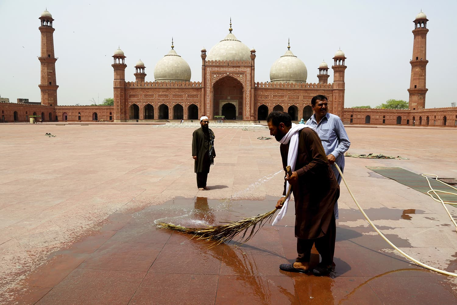 Pakistanis wash the courtyard of the historical Badshahi Mosque in preparation for the month of Ramazan in Lahore, Pakistan on Wednesday. — AP