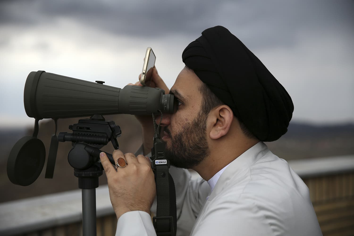 Iranian cleric Mohammad Hossein Dehsorkhi looks through binoculars for the new moon that signals the start of the Islamic holy month of Ramazan, at the Imam Ali observatory about 45 kilometres outside the holy city of Qom, south of the capital Tehran, Iran on Wednesday. - AP